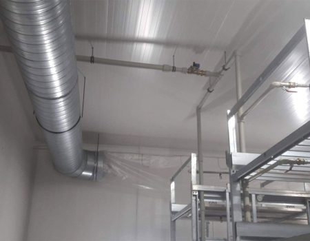 Fragment pomieszczenia z instalacją do nawadniania upraw oraz regałami
